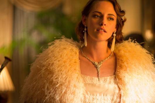 "A still from ""Cafe Society"" showing Kristen Stewart in a custom-made light pink silk and lace Chanel dress and Chanel fine jewelry"