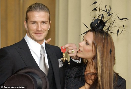 England football captain David Beckham stands with his wife, Victoria, as he shows off the OBE (Officer of the Order of the British Empire) he received, from Britain's Queen Elizabeth II at London's Buckingham Palace. The former Manchester United star, who now plays for Real Madrid, said recently: 'I am honoured and privileged to receive this recognition. It's not just for me but for Manchester United, England, all of my team mates and my family'.